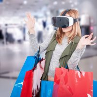 Woman feeling scared when using virtual reality glasses in shopping mall